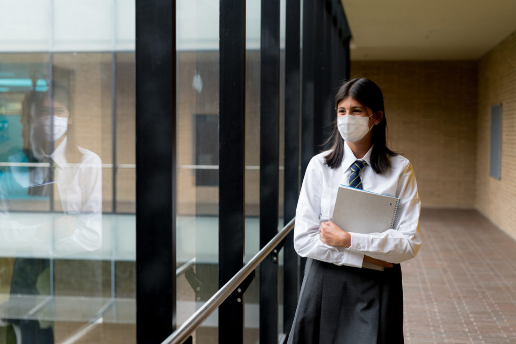 Happy student at the school wearing a facemask to avoid an infectious disease - COVID-19 pandemic lifestyle concepts